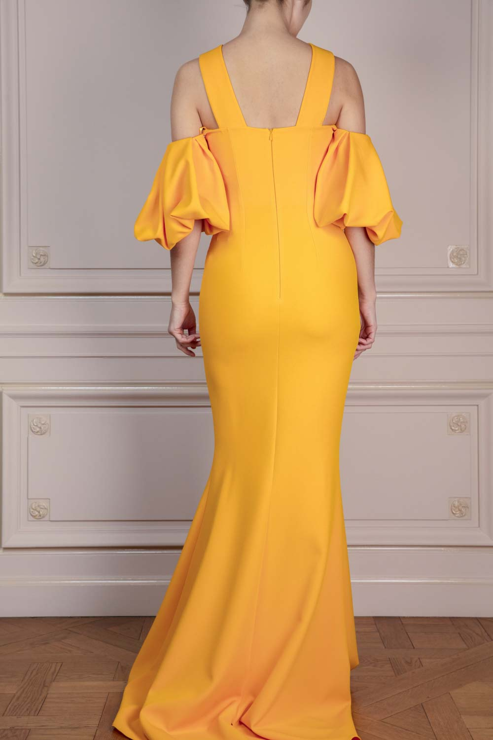 Floor-length gown in Marigold Yellow stretch crepe with boat neckline, open shoulders, pleated balloon sleeves and a fishtail train.